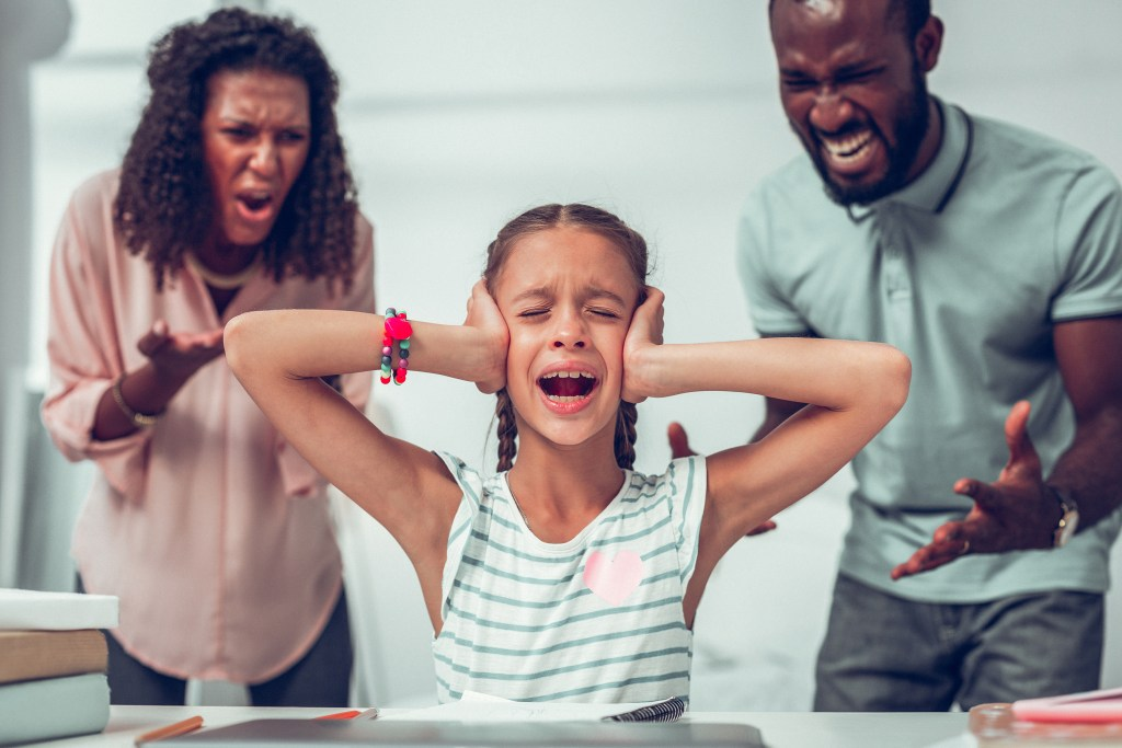 Upset Girl Closing Ears While Her Parents Yelling At Her.