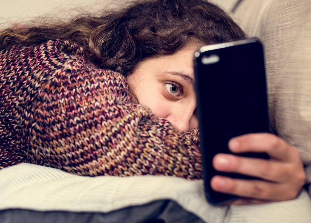 Teenage girl using a smartphone on a bed