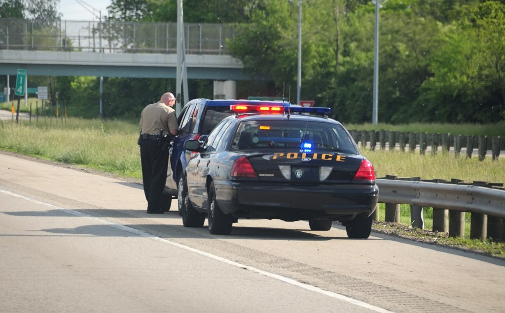 A police cruiser with the lights flashing has stopped a speeding car along the interstate highway and is issuing a ticket.