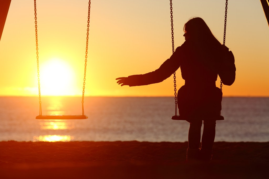 Single woman alone missing a boyfriend while swinging on the beach at sunset