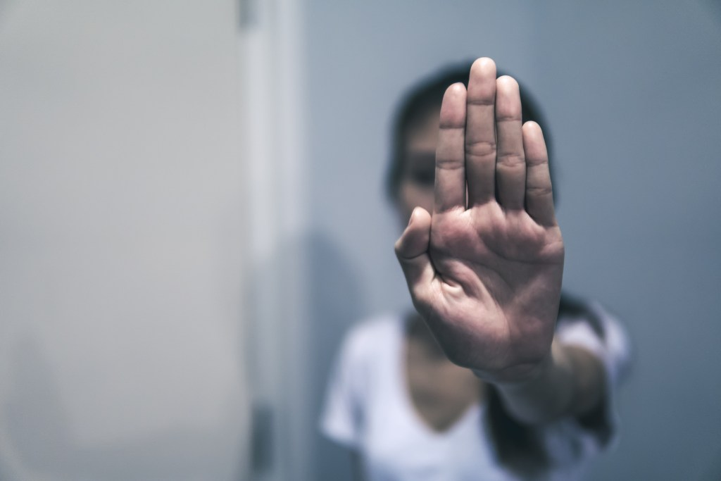 Women abused holding her hand up. Stop sexual harassment against women.