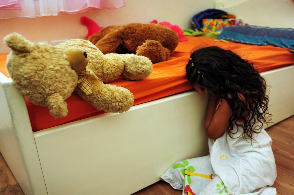 Child abuse image, little girl with hands in face as if crying by her bed. physical and/or psychological/emotional image