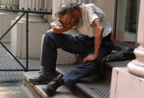 Homeless man with head in hands, desperate, sitting on steps.