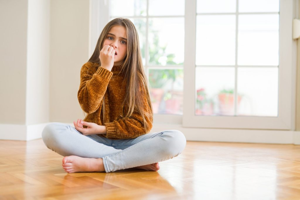 young girl kid sitting on the floor at home looking stressed and nervous with hands on mouth biting nails.