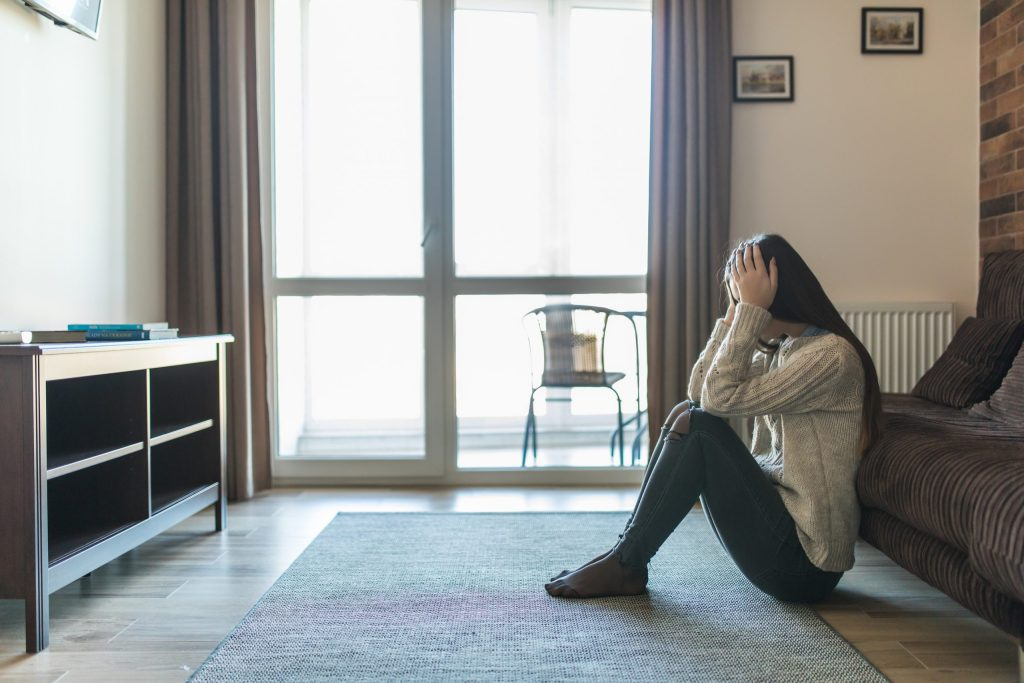 young depressed woman sitting on floor worried