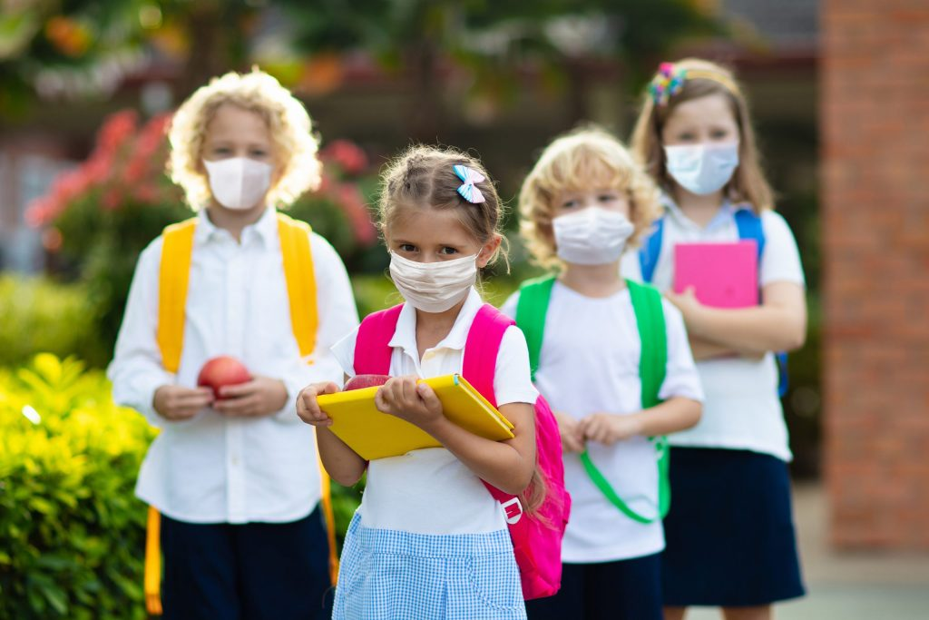 Boys and girls going back to school after covid-19 quarantine and lockdown. Group of kids in masks for coronavirus prevention.