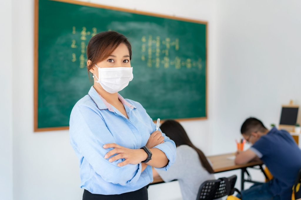 Asian woman teacher wearing masks to prevent the outbreak of Covid 19 in classroom with student while back to school reopen their school.