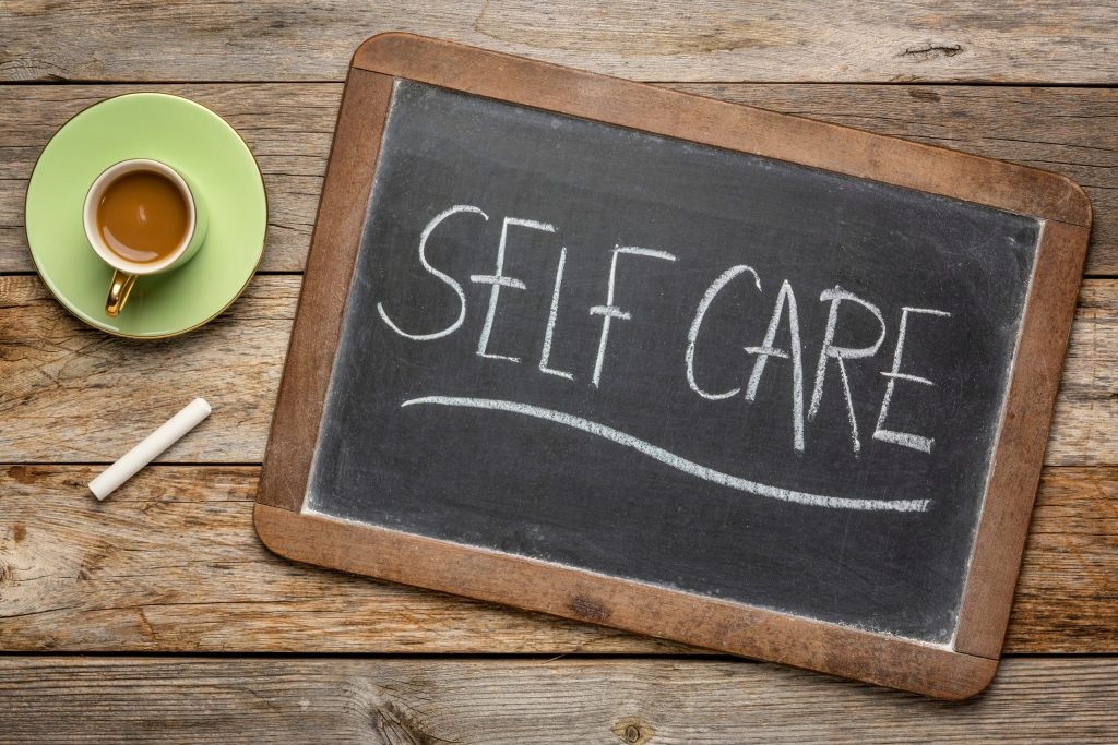 Self care - white chalk handwriting on a blackboard with a cup of coffee, lifestyle concept