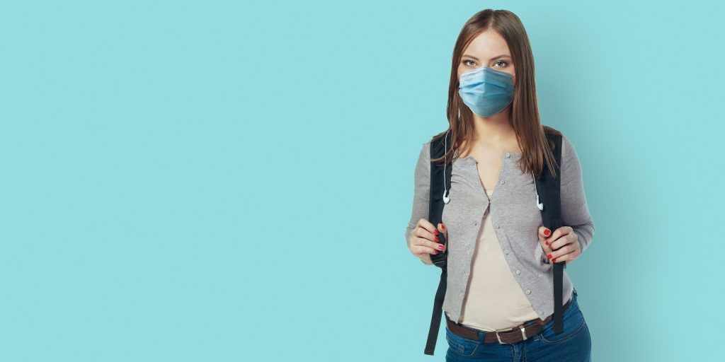 Student wearing face mask standing against blue wall with backpack. Safe back to school during pandemic concept. New normal high school education.