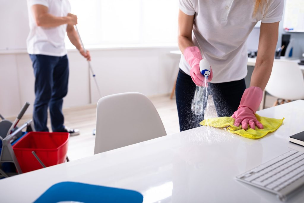 Two Janitor Cleaning The Desk And Mopping Floor In a classroom.