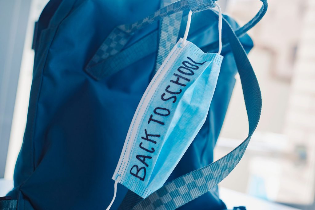 closeup of a green bookbag and a blue surgical mask with the text back to school written in it,