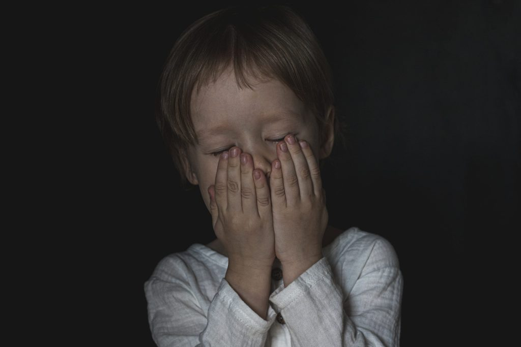 Portrait of a scared little boy child. The kid covered his mouth with his hands, closed his eyes. due to stress and shock.