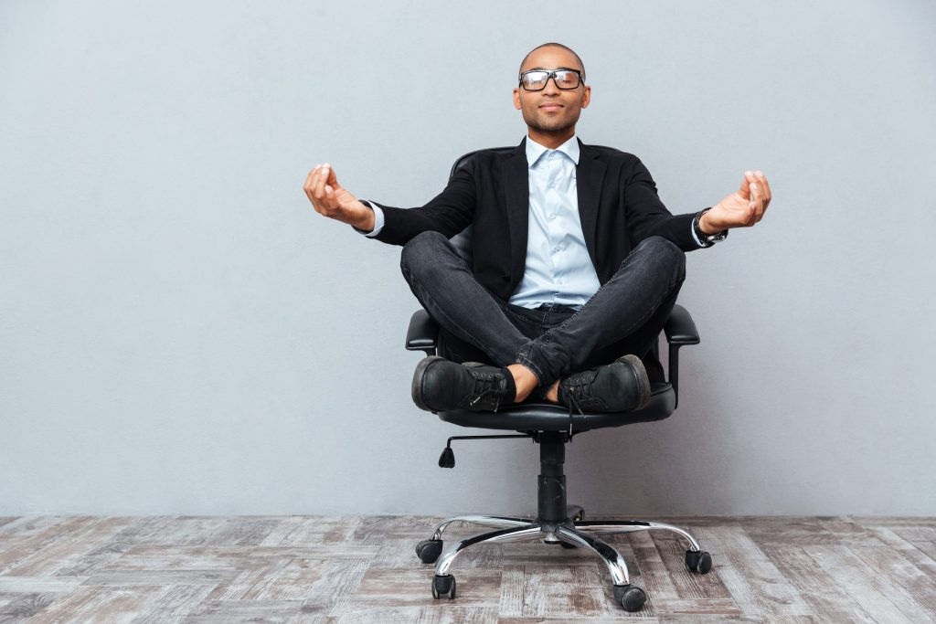 African American man sitting and meditating on office chair