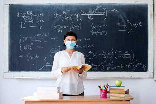 Teacher with face mask welcoming children back at school after lockdown. Back to school during COVID-19 pandemic.