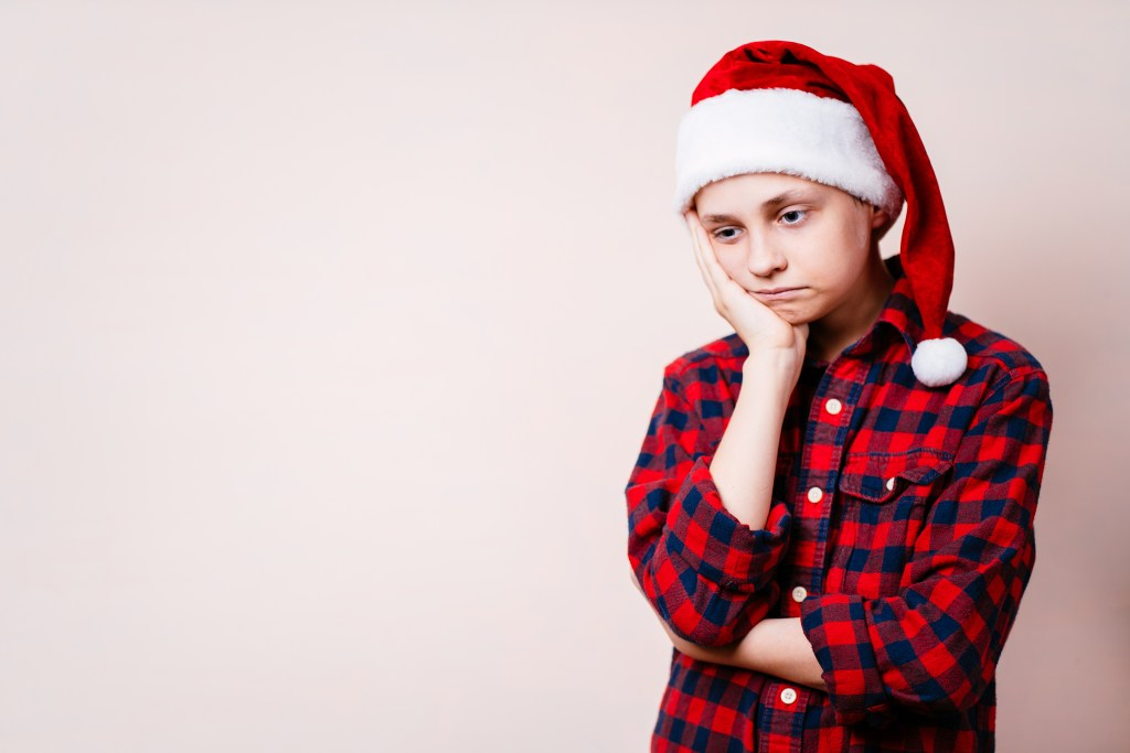 bored and pensive kid in christmas hat.
