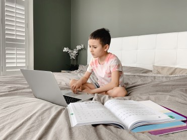 Boy sitting in bed and learning online on laptop. Virtual class lesson on video.