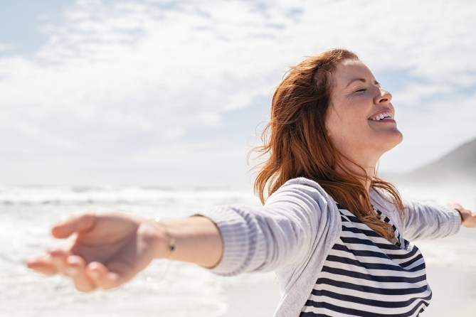 Happy redhead woman relaxing with arms outstretched at beach with eyes closed feeling free at sea.