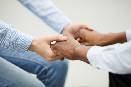 Closeup of two people holding hands heartily during therapy se4ssion in support group, copy space