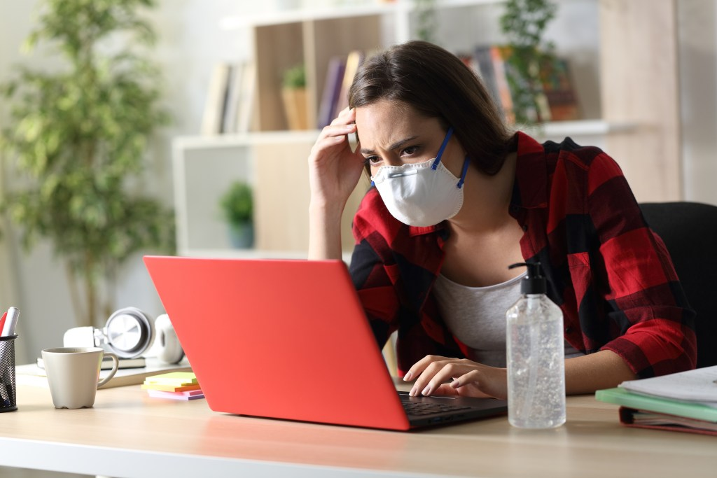 Sad student with protective mask reading bad coronavirus news on laptop sitting on a desk at home