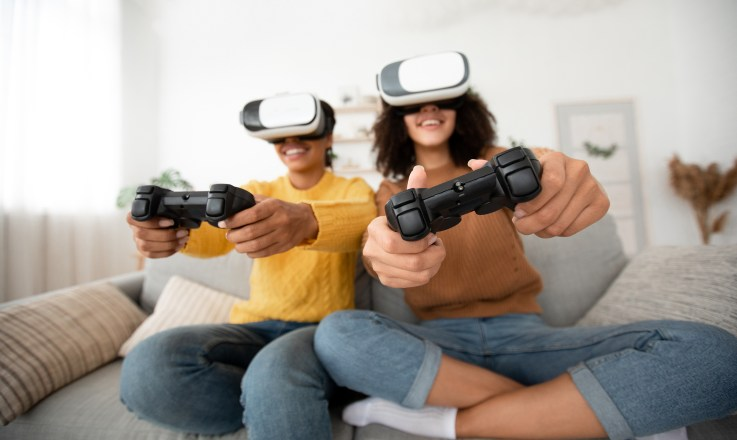 2 teen girls have fun on couch in cozy interior with video games. Enthusiastic smiling teen african american in VR glasses with gamepads, emotional playing in living room, free space