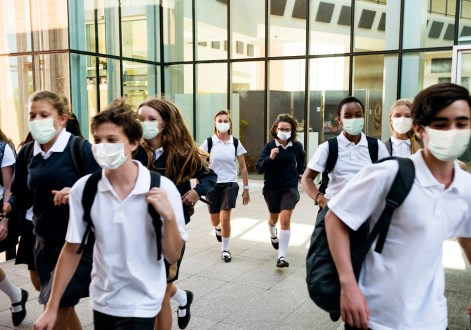 High school students wearing masks on their way home