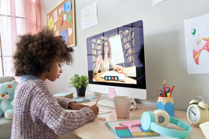 African American school kid girl distance learning by video conference chat with remote teacher, online tutor teaching digital class, web lesson on computer at home. Virtual education.