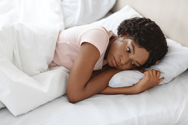 Depressed young black woman lying in bed alone and feeling lonely, spending day in bed