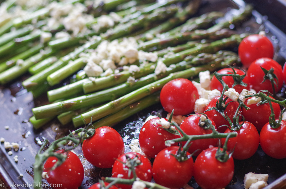 Bright green braised asparagus laid out on a baking sheet with white feta sprinkled on top in front of bright red cherry tomatoes