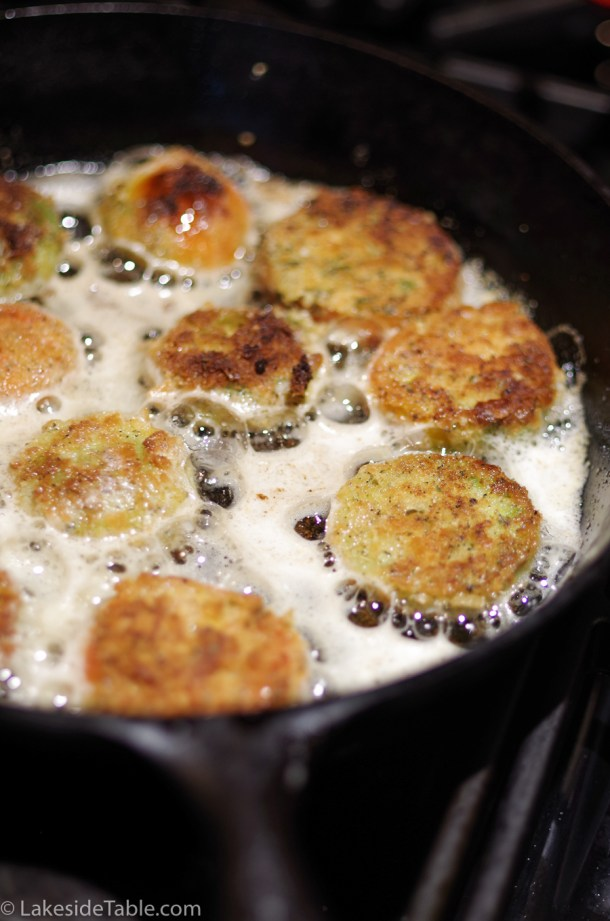 Golden brown fried green tomatoes frying in a cask iron skillet