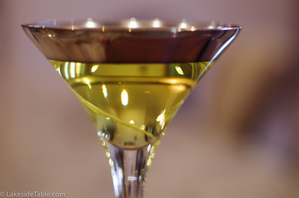 martini glass with silver band and light yellow turmeric infused vodka