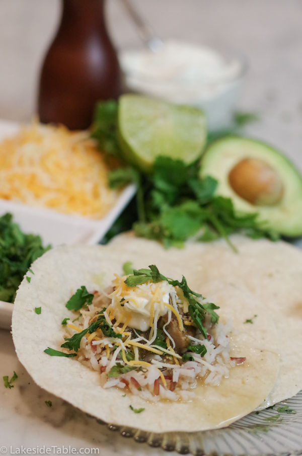 pork chili verde on tortillas with cheese, avocado and lime