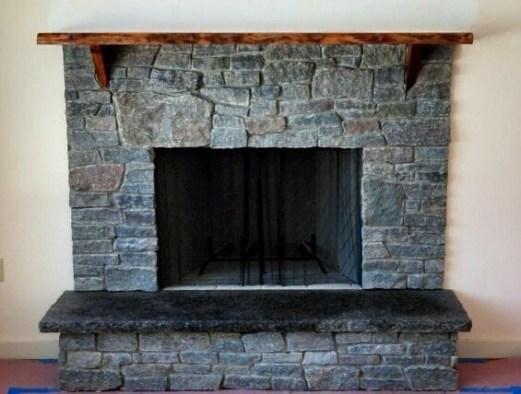 Dark ledge stone fireplace with rustic mantel