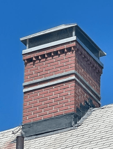 Full chimney rebuild with granite accents and hip and ridge cap