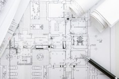 Architectural blueprints and blueprint rolls with magnifying glass