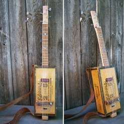 "Vintage cigarbox, flame maple-koa neck, 13 frets, 19"" scale Ted Crocker ""Stonehenge"" pick-ups, Grover machines 29"" x 5.5"" x 5.5"" $1,200.00"
