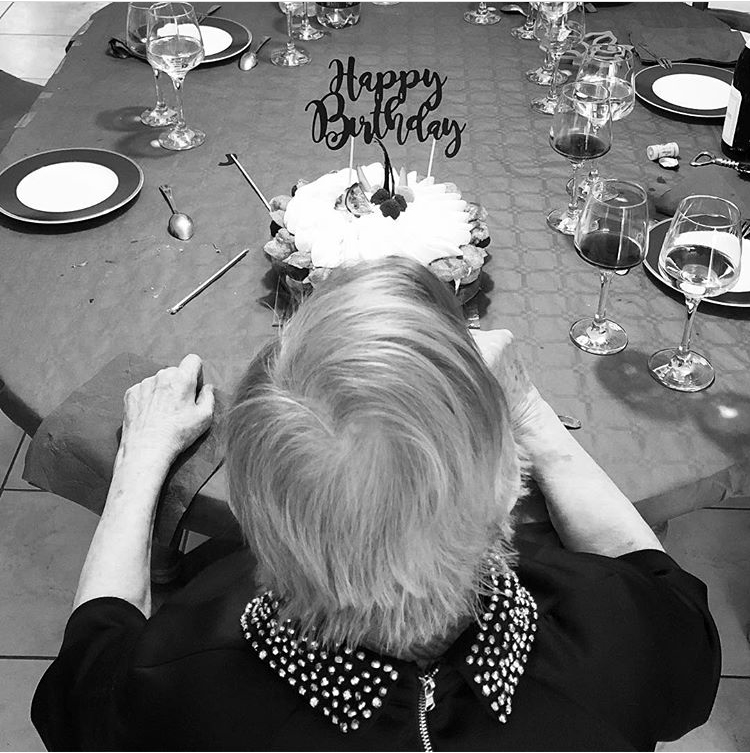 """C'est gratienne de dos devant un gâteau avec une inscription en volume dessus écrit """" HAPPY BIRTHDAY""""."""