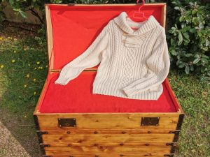 Pull irlandais en coton présenté sur une malle ancienne restaurée.