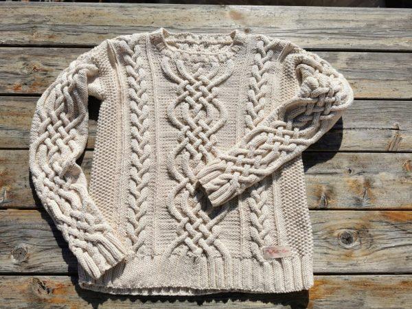 Pull irlandais tricoté main à torsade ronde présenté à plat. La Malle au Coton