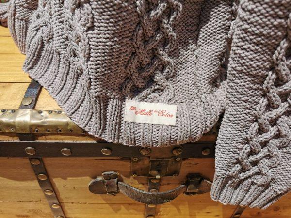 Fisherman sweater. Détail des points et de l'étiquette de la marque sur malle ancienne