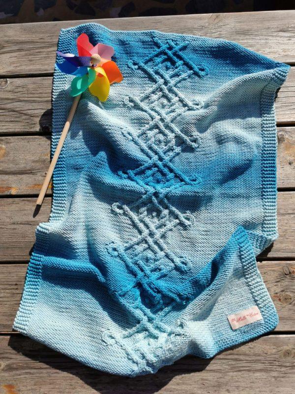 Couverture bébé bleu lagon tricotée main présentée dans son ensemble sur une table au soleil