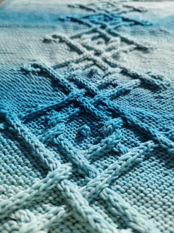 Détail sur les mailles et la torsade de la couverture pour bébé lagon