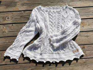 Pull blanc présenté en entier sur une table au soleil