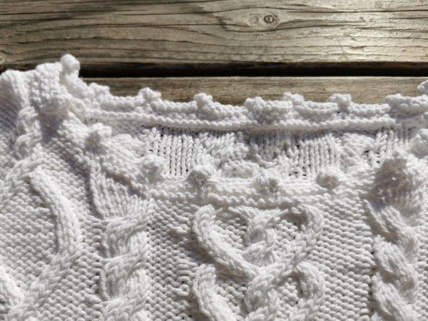 Pull blanc tricoté à la main en coton blanc. Détail de l'encolure