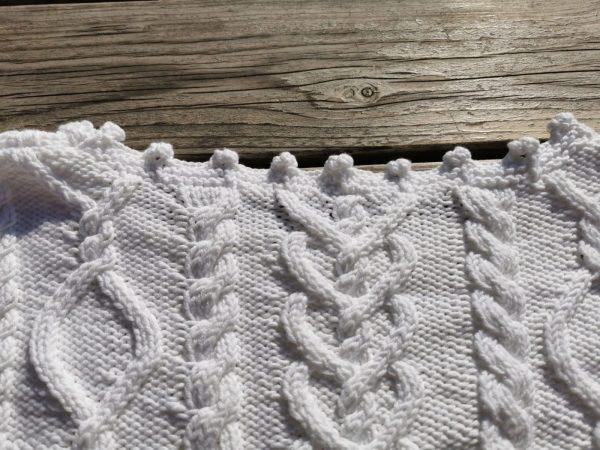 Détail de la fine encolure du pull blanc, côté dos. Un détail de qualité