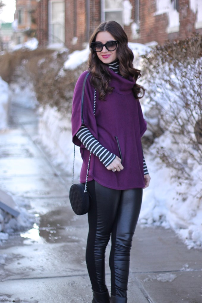 purple poncho with leather details and grey striped turtleneck