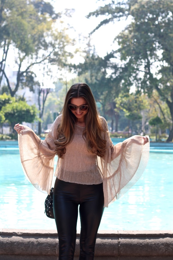 Beige bell sleeve top, black patent leather pants
