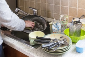 man washing dirty dishes in the kitchen sink