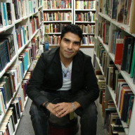 Image of a person in a black sports coat, kneeling amongst shelves of archival books.
