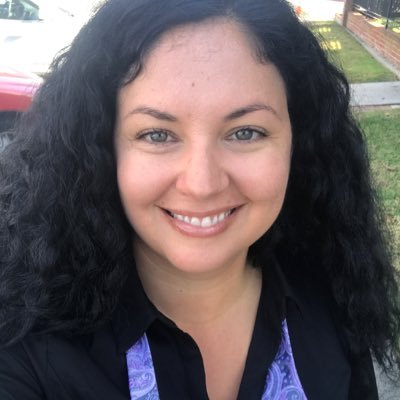 Image of a person with curly dark hair, smiling at the camera.