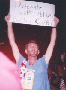 "Image of a person holding up a sign high overhead which reads, ""Delegate with AIDS seeks CURE""."